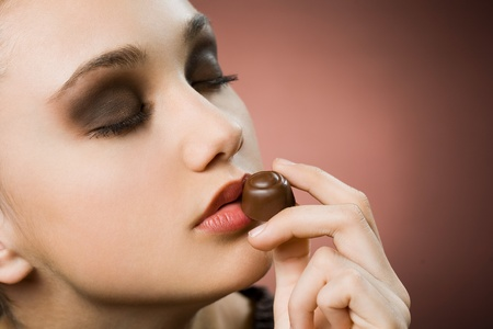 pralines: Very beautiful young brunette woman tasting fine chocolate.