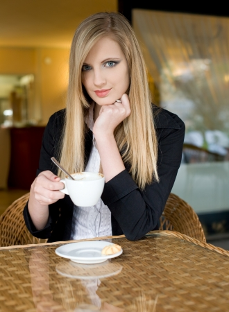 gorgeous businesswoman: Portrait of a beautiful elegant young blond woman having coffee. Stock Photo