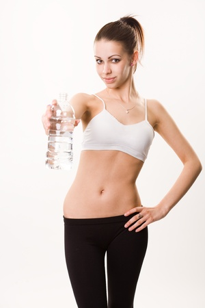 Stay hydrated, portrait of young slender fitness brunette with bottle of water. photo