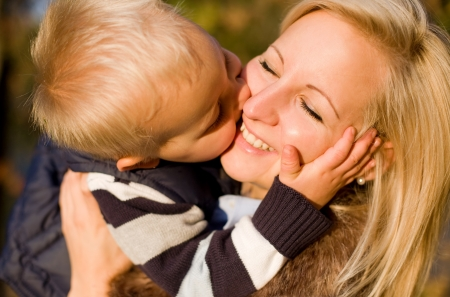 Big kiss for mom, cute young boy kissing his mother. photo