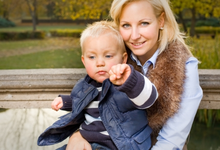 Attractive young mom and son portrait, outdoors in the park at fall. photo