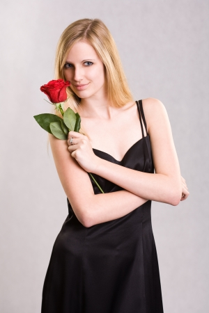 Glamouros young blond with rose in elegant long black dress. photo