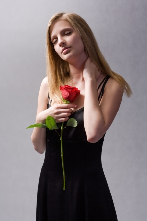 Moody portrait of elegant blonde with big vibrant red rose. photo