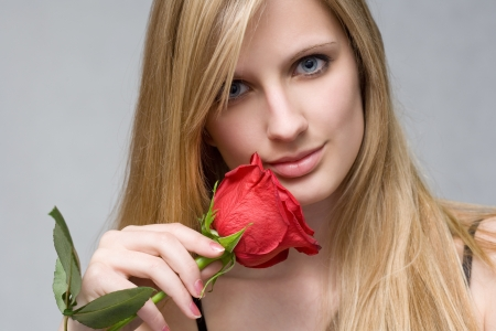 Moody portrait of romantic blond with vibrant fresh red rose. photo