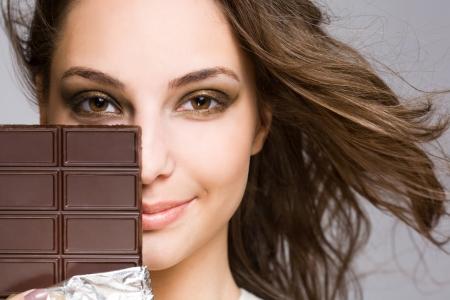 Chocolate seduction, portrait of a brunette beauty with tasty dark chocolate. Фото со стока - 13857259