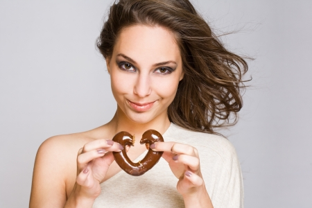 heartbreaker: Portrait of an attractive young brunette with shiny chocolate heart. Stock Photo