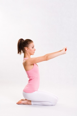 kneeling woman: Portrait of a flexible young yoga girl in pink top.