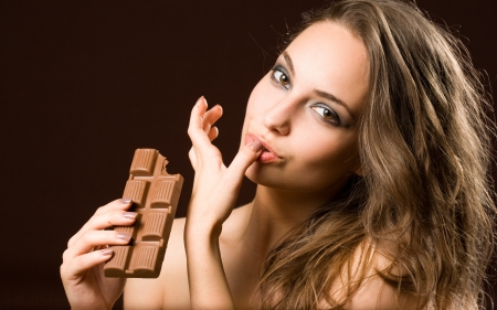 Sensual chocolate fun, young brunette beauty tasting chocolate. photo