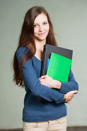 slender: Portrait of a gorgeous young brunette student girl with laptop and exercis books.
