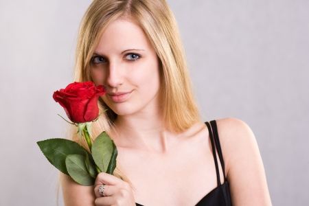Portrait of a beautiful romantic young blond in elegant dress with red rose. photo