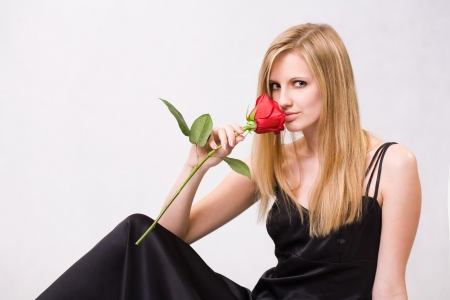 Romantic portrait of a gorgeous young blond woman holding big red rose. photo