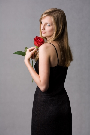 feminine beauty: Romantic portrait of a gorgeous young blond woman holding big red rose. Stock Photo