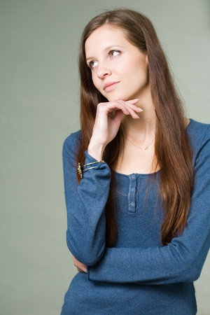 skinny girl: Portrait of a pretty young brunette student girl pondering.