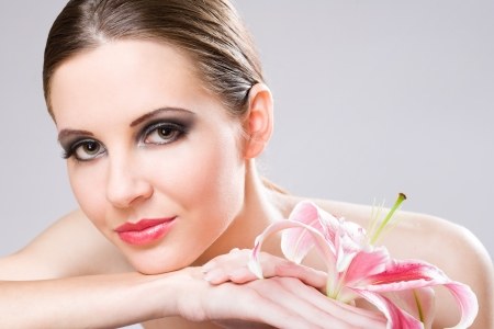 Beauty shot of beautiful young brunette woman with colorful lily flower. photo