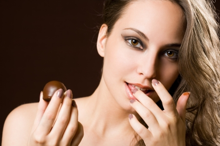 finger licking: Sensual chocolate girl, portrait of a young b brunette beauty.