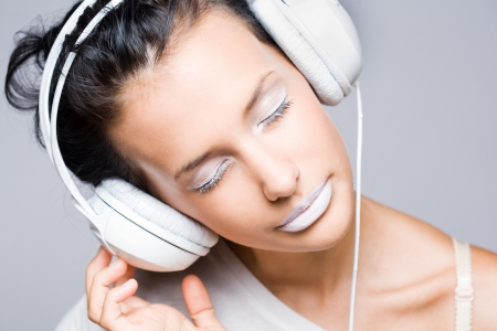 sexy headphones: Dreamy young music lover, beautiful young brunette wearing big white headhones. Stock Photo