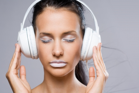 Dreamy young music lover, beautiful young brunette wearing big white headhones. photo