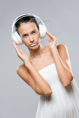 White noise, gorgeous young brunette woman listening to music in headphones. photo