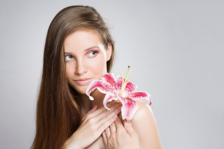beauty shot: Gorgeous young bruinette beauty shot with colorful flower and makeup.