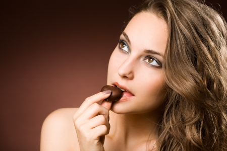 eating chocolate: Portrait of a chocolate loving young brunette beauty Stock Photo