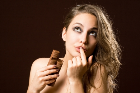 finger licking: Portrait of a chocolate loving young brunette beauty Stock Photo