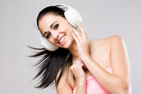 Portrait of a brunette beauty enjoying music in white headphones  photo