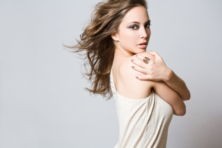 Half length portrait of a beautiful brunette with windswept hair. photo