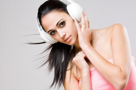 Portrait of a brunette beauty wearing white headphones. photo