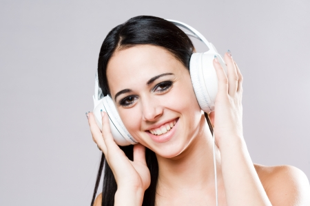 Gorgeous brunette music lover wearing bright white headhones  photo