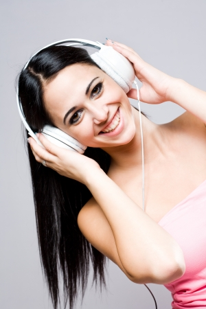 Portrait of a gorgeous fashionable young brunette listening to music  photo