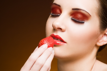 Sweet fruit craving, young brunette with strawberry. photo
