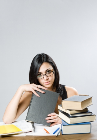 Portrait of a cute young brunette student girl with large pile of books. Stock Photo - 14624199