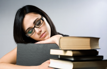 Portrait of a cute young brunette student girl with large pile of books. Stock Photo - 14624205