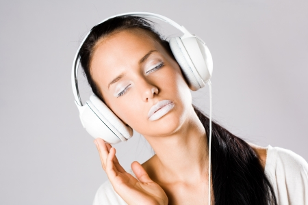 sexy headphones: White noise, young brunette listening to music in white headphones, creative makeup. Stock Photo
