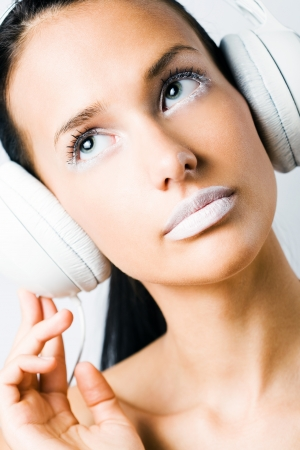 White noise, young brunette listening to music in white headphones, creative makeup. photo