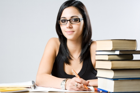 Portrait of a cute young student girl with large pile of books. Stock Photo - 14838413