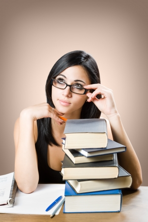 Portrait of a cute young student girl with large pile of books. Stock Photo - 14838400