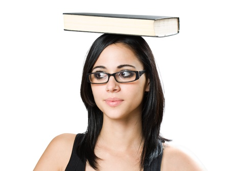 Balancing act, portrait of cute young student girl eith book on top of her head. Stock Photo - 14838425