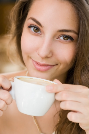 Portrait of a beautiful young brunette woman enjoying coffee. photo