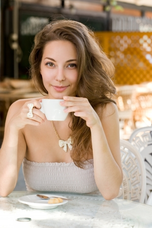 Portrait of a beautiful young brunette woman enjoying coffee. photo