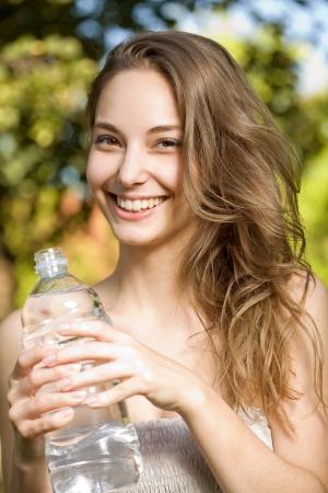 the thirst: Splendida giovane donna bruna in possesso di una bottiglia di acqua fresca fresca.