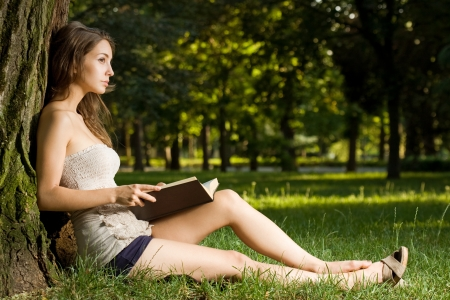 Portrait of a gorgeous brunette woman reading a  book in the park  photo