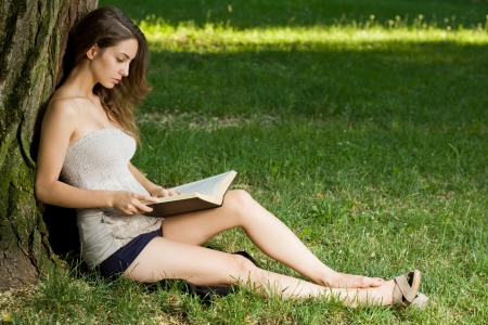 Portrait of a beautiful young brunette woman enjoying book outdoors  photo