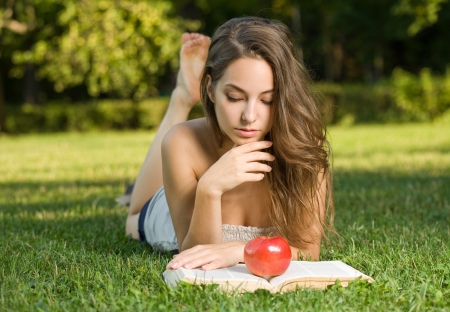 Portrait of a beautiful brunette woman studying outdoors reading a book  photo