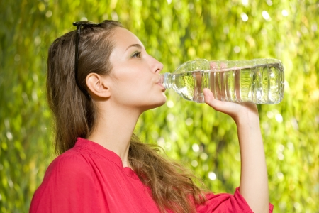 Precious cool water, gorgeous young brunette with bottled water  photo