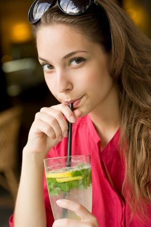 Big glass of refreshment, beautiful young brunette woman drinking lemonade  photo