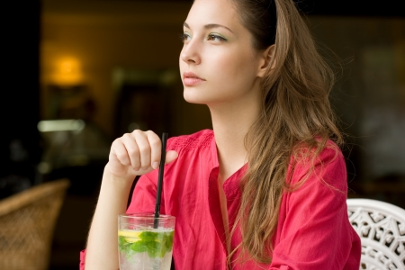 Big glass of refreshment, beautiful young brunette woman drinking lemonade  photo