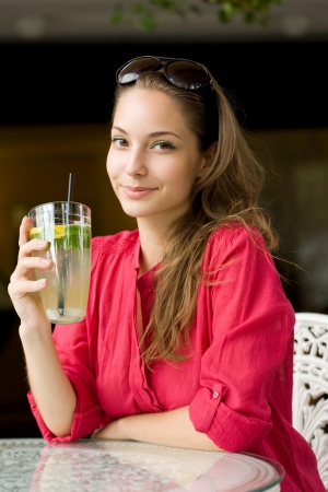 Summer heat refreshment, grogeous young brunette drinking lemonade  photo