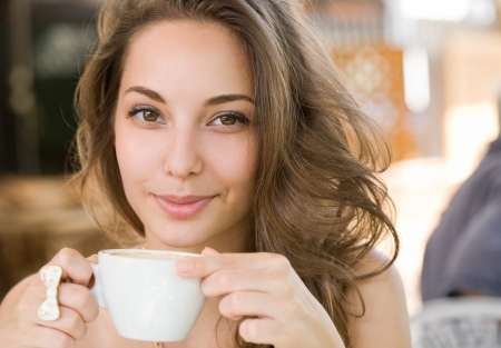 women holding cup: Portrait of a young brunette beauty enjoying her coffee.