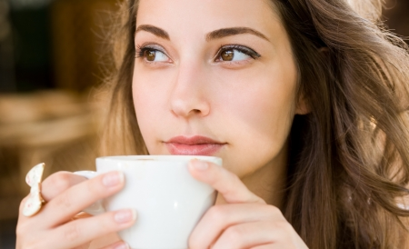 Closeup portrait of a beautiful young woman having coffee. photo